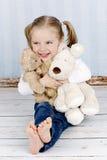 Αγκαλιά μικρών κοριτσιών με τα παιχνίδια βελούδου στοκ φωτογραφίες