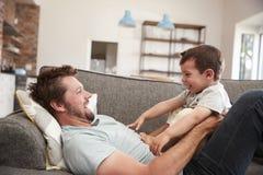 Αγκαλιά πατέρων και γιων στον καναπέ από κοινού στοκ φωτογραφία