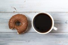 Δαγκωμένα doughnut σοκολάτας και φλυτζάνι του μαύρου καφέ, τοπ άποψη στο ξύλινο υπόβαθρο Στοκ Φωτογραφίες