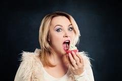 δαγκώνοντας γυναίκα κέικ Πρότυπο με τα ανθυγειινά τρόφιμα στοκ εικόνα