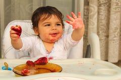 Αγοράκι ενός έτους βρεφών που τρώει strawberryes και που εξετάζει το βρώμικο μικρό χέρι του στοκ εικόνες