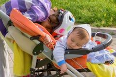 Αγοράκι και ο ύπνος αδελφών του σε έναν περιπατητή Στοκ φωτογραφία με δικαίωμα ελεύθερης χρήσης