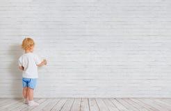 Αγοράκι με τη βούρτσα χρωμάτων που στέκεται πίσω κοντά στο τουβλότοιχο στοκ εικόνες
