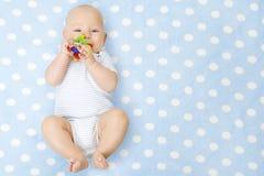 Αγοράκι με το παιχνίδι Teether στο στόμα που βρίσκεται πέρα από το μπλε υπόβαθρο, ευτυχές στοκ φωτογραφία