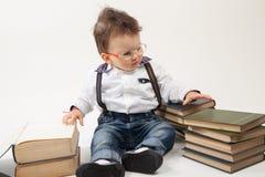 Αγοράκι με eyeglasses που εξετάζει ένα βιβλίο στοκ φωτογραφία με δικαίωμα ελεύθερης χρήσης