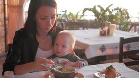 Αγοράκι μικρών παιδιών και μητέρα στον καφέ, μωρό στο εστιατόριο Λίγο αγοράκι που έχει το κομμάτι του ψωμιού απόθεμα βίντεο