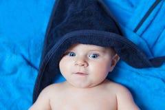Αγοράκι παιδάκι ενάντια στην μπλε πετσέτα λουτρών Στοκ εικόνες με δικαίωμα ελεύθερης χρήσης
