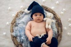 Αγοράκι που βρίσκεται σε ένα καλάθι με το καπέλο-πλέξιμο γουνών Στοκ εικόνα με δικαίωμα ελεύθερης χρήσης