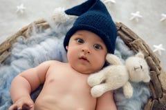 Αγοράκι που βρίσκεται σε ένα καλάθι με το καπέλο-πλέξιμο γουνών Στοκ Εικόνα