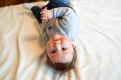 Αγοράκι στην άσπρη ηλιόλουστη κρεβατοκάμαρα Νεογέννητη χαλάρωση παιδιών στο κρεβάτι Βρεφικός σταθμός για τα μικρά παιδιά Οικογενε στοκ φωτογραφία με δικαίωμα ελεύθερης χρήσης