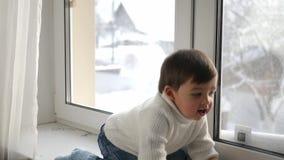 Αγοράκι στην άσπρη πλεκτή συνεδρίαση πουλόβερ από το παράθυρο το χειμώνα φιλμ μικρού μήκους