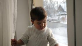Αγοράκι στην άσπρη πλεκτή συνεδρίαση πουλόβερ από το παράθυρο το χειμώνα απόθεμα βίντεο