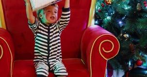 Αγοράκι στο χριστουγεννιάτικο δέντρο με το δώρο απόθεμα βίντεο