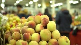 Αγορά των υγιών τροφίμων Οι άνθρωποι πηγαίνουν σε ένα υπόβαθρο Ροδάκινα στο πρώτο πλάνο απόθεμα βίντεο