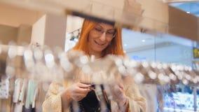Αγορές για τη γυναίκα Το κορίτσι εξετάζει μια τιμή θαμπάδων Στοκ φωτογραφία με δικαίωμα ελεύθερης χρήσης