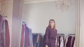 Αγορές, ενδύματα, το ευτυχές, όμορφο κορίτσι μόδας, ύφους και έννοιας ανθρώπων - φορά ένα φόρεμα και πηγαίνει να κοιτάξει απόθεμα βίντεο