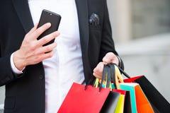 Αγορές στη Δευτέρα cyber ή τη μαύρη πώληση Παρασκευής Νέα τεχνολογία για τη επιχειρησιακή επικοινωνία Τσάντες και smartphone αγορ Στοκ φωτογραφία με δικαίωμα ελεύθερης χρήσης