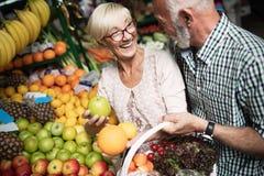 Αγορές, τρόφιμα, πώληση, καταναλωτισμός και έννοια ανθρώπων - ευτυχές ανώτερο ζεύγος που αγοράζει τα φρέσκα τρόφιμα στοκ εικόνες