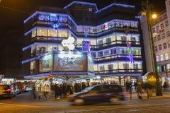 Αγορές Χριστουγέννων μπροστά από ένα μεγάλο διακοσμημένο εμπορικό κέντρο Kotva στην Πράγα στο τετράγωνο Δημοκρατίας Στοκ Φωτογραφία