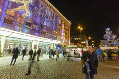 Αγορές Χριστουγέννων μπροστά από ένα μεγάλο διακοσμημένο παλλάδιο εμπορικών κέντρων στην Πράγα στο τετράγωνο Δημοκρατίας Στοκ φωτογραφίες με δικαίωμα ελεύθερης χρήσης