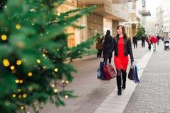αγορές Χριστουγέννων Όμορφη ευτυχής γυναίκα στο κόκκινο φόρεμα και lethe Στοκ Φωτογραφία