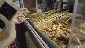 Αγοραστές που δείχνουν στα κινεζικά τρόφιμα οδών απόθεμα βίντεο