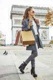 Αγοραστής γυναικών κοντά Arc de Triomphe που έχει τον καφέ και macaroon Στοκ Εικόνες