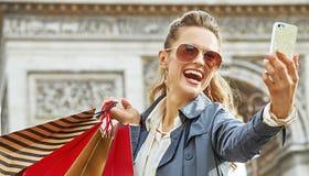 Αγοραστής γυναικών κοντά Arc de Triomphe που παίρνει selfie με το κινητό τηλέφωνο Στοκ Φωτογραφία