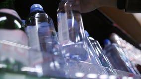 Αγοραστής γυναικών που παίρνει το μπουκάλι νερό στην υπεραγορά Ποτό αγοράς κοριτσιών Vegan 4K σε αργή κίνηση απόθεμα βίντεο