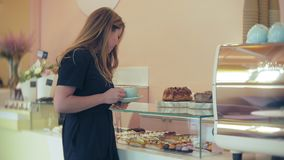 Αγοραστής επιλέγει yummy Το νέο ελκυστικό κορίτσι, γυναίκα αγοράζει στη καφετερία ή τις ζύμες, κέικ, κέικ, macaroon Α απόθεμα βίντεο