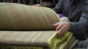 Αγοραστής νεαρών άνδρων που επιλέγει τον τάπητα που καλύπτει για το σπίτι του στη λεωφόρο αγορών 4k φιλμ μικρού μήκους