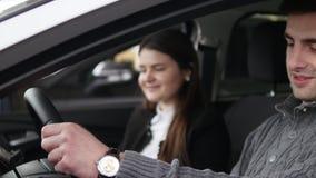 Αγοραστής που έχει τη συνομιλία με τον πωλητή αυτοκινήτων κατά τη διάρκεια της επιθεώρησης του αυτοκινήτου φιλμ μικρού μήκους