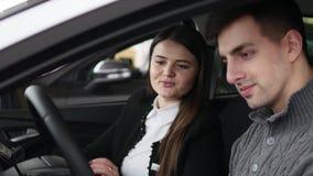 Αγοραστής που έχει τη συνομιλία με τον πωλητή αυτοκινήτων κατά τη διάρκεια της επιθεώρησης του αυτοκινήτου απόθεμα βίντεο