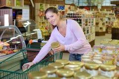 Αγοραστής που τοποθετεί την κονσέρβα βάζων στο καροτσάκι αγορών στην υπεραγορά Στοκ Εικόνες