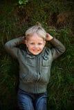 Αγοροκόριτσο που βρίσκεται στη χλόη και το χαμόγελο Στοκ Εικόνες