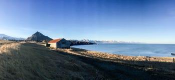 Αγροικία, παραλία, βουνό, μπλε ουρανός, Arnarstapi, Ισλανδία Στοκ εικόνα με δικαίωμα ελεύθερης χρήσης