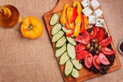 Αγροτικά φρέσκα λαχανικά με φέτα και ελιές στο αγροτικό ξύλινο BO Στοκ Εικόνες