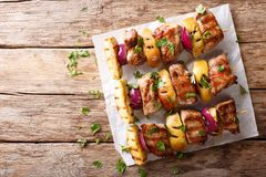 Αγροτικά juicy kebabs του χοιρινού κρέατος με τα μήλα και την κόκκινη κινηματογράφηση σε πρώτο πλάνο κρεμμυδιών Στοκ εικόνα με δικαίωμα ελεύθερης χρήσης
