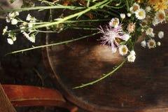 Αγροτική ανθοδέσμη των άγριων λουλουδιών στην παλαιά ξύλινη καρέκλα στη θερινή ημέρα Στοκ εικόνες με δικαίωμα ελεύθερης χρήσης