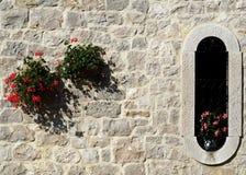 Αγροτική διακόσμηση Λουλούδια στον εξωτερικό τοίχο της πέτρας και στο αρχαίο ελλειπτικό παράθυρο Στοκ Εικόνες