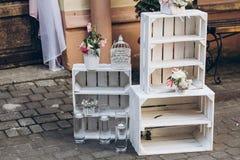Αγροτική ζώνη γαμήλιων φωτογραφιών άσπρα κιβώτια με τα λουλούδια και τα κεριά Στοκ Φωτογραφία