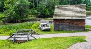 Αγροτική καμπίνα με την ξεπερασμένη βάρκα και την ξύλινη γέφυρα ποδιών Στοκ Εικόνες