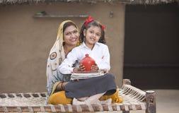 Αγροτική μητέρα με τα χρήματα αποταμίευσης κορών στη piggy τράπεζα για τη μελλοντική εκπαίδευση στοκ εικόνες με δικαίωμα ελεύθερης χρήσης