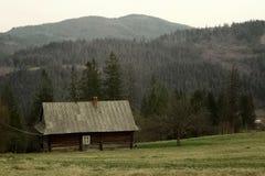 Αγροτική ξύλινη καμπίνα στους λόφους στο υπόβαθρο των βουνών και Στοκ Εικόνες