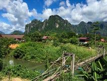 Αγροτική περιοχή στο Λάος με την ξύλινη γέφυρα που διασχίζει τον ποταμό Στοκ φωτογραφία με δικαίωμα ελεύθερης χρήσης