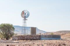 Αγροτική σκηνή με water-pumping τον ανεμόμυλο και το φράγμα σε Bergsig Στοκ Εικόνες