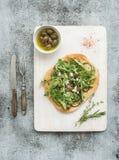 Αγροτική σπιτική πίτσα με eggpant, το τυρί, τις ελιές και το arugula στο λευκό ξύλινο εξυπηρετώντας πίνακα πέρα από το γκρίζο σκη Στοκ εικόνες με δικαίωμα ελεύθερης χρήσης