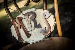 Αγροτική συνεδρίαση γαμήλιων σημαδιών σε μια καρέκλα Στοκ Εικόνες