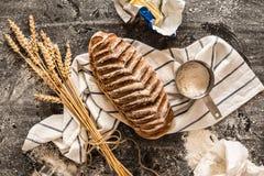 Αγροτική φλοιώδης φραντζόλα του ψωμιού και των συστατικών στο Μαύρο στοκ φωτογραφία