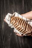 Αγροτική φλοιώδης φραντζόλα του ψωμιού στα χέρια αρτοποιών ` s στο Μαύρο στοκ εικόνες